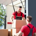 Male removalists in Liverpool unloading In a van and passing boxes