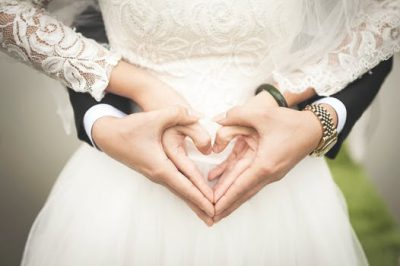 wedding couple creating a heart hand symbol