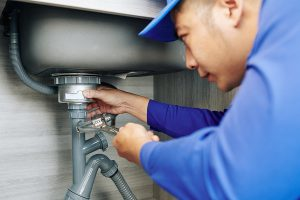 Blocked drain plumber in Canberra using wrench to repair the drain
